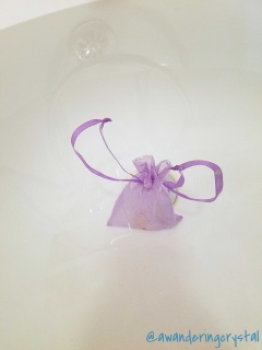 A purple mesh bag is floating near the bottom of a white bath tub with the ribbons floating to the sides like angel wings.